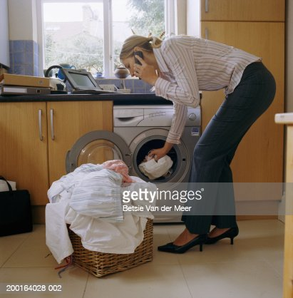 Businesswoman taking laundry out of machine, using mobile phone : Stock Photo