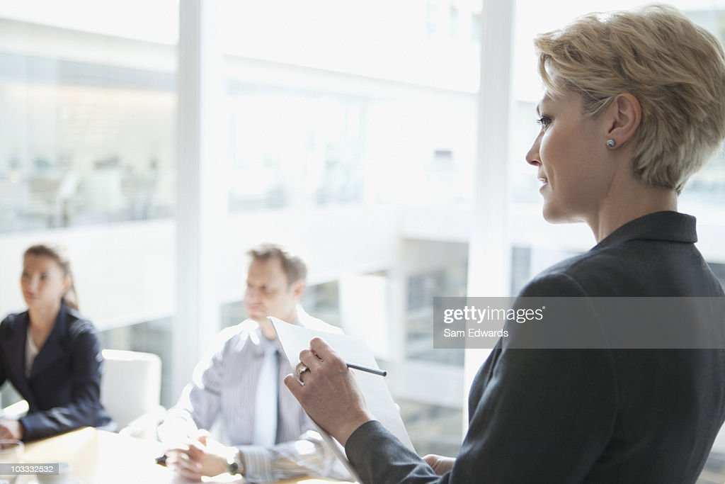 Businesswoman taking notes in meeting : Stock Photo