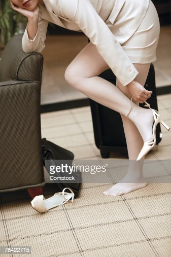 businesswoman taking off shoes while standing stock photo | getty