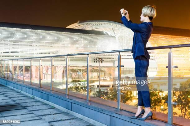Geschäftsfrau, Fotografieren mit Smartphone auf Steg von Flughafen/Bahnhof
