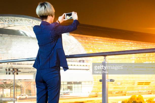 businesswoman taking photos with smartphone on footbridge of airport/station