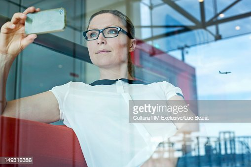 Businesswoman taking picture in airport : Stock Photo