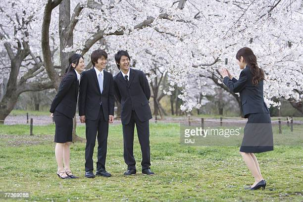 Businesswoman Taking Picture of Co-workers Under Cherry Trees, Smiling, Full Length, Side View