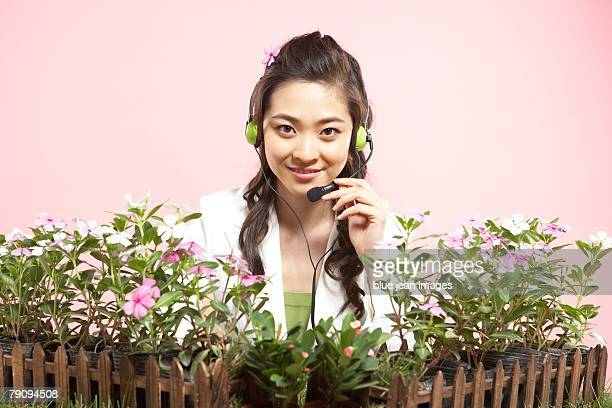 Businesswoman talking into a headset amidst potted flowers.