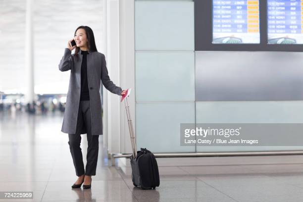 Businesswoman talking on cell phone at the airport