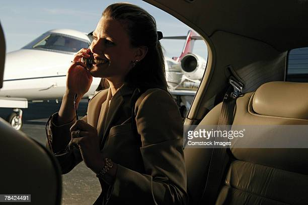 Businesswoman talking on cell phone in car at airport