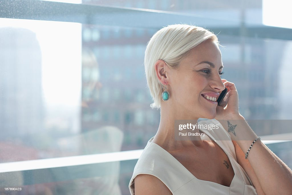 Businesswoman talking on cell phone in office : Stock Photo