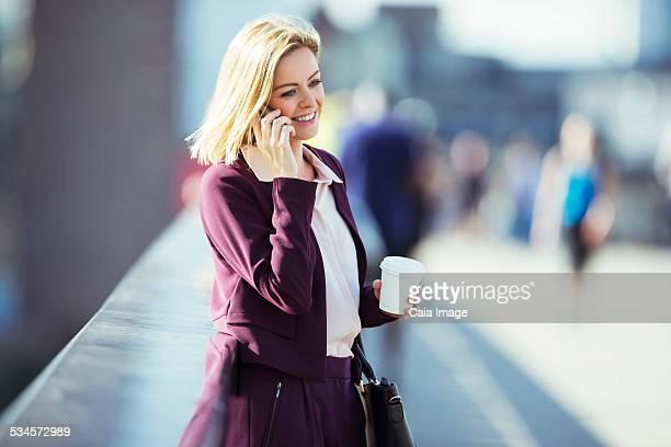 Businesswoman talking on cell phone on urban bridge