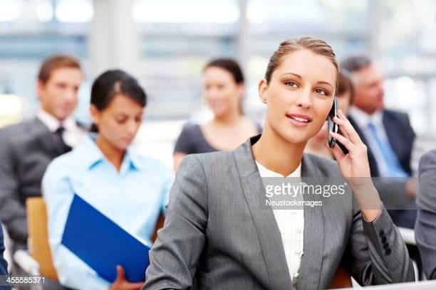 Femme d'affaires parler sur téléphone portable lors d'une conférence