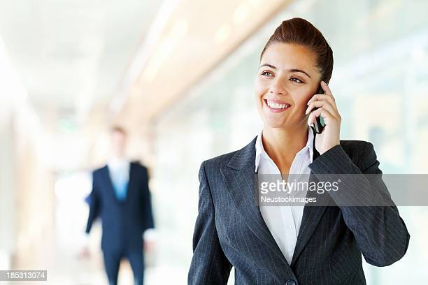 Businesswoman Talking On Mobile Phone At Airport
