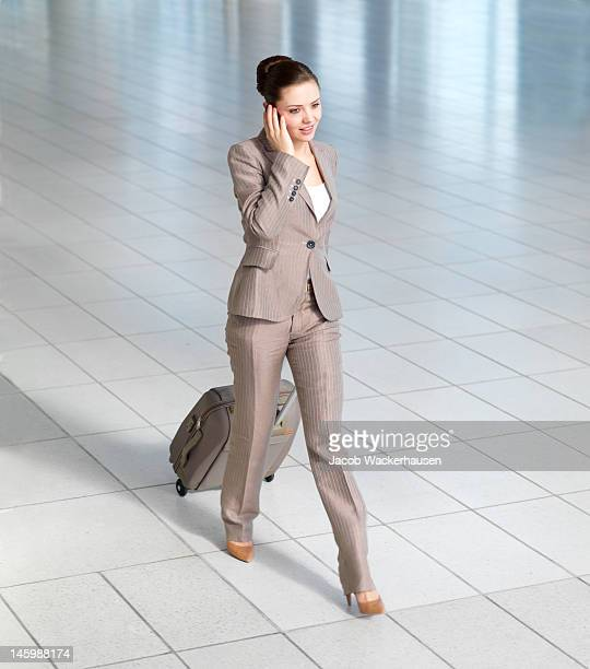 Businesswoman talking on mobile phone in airport