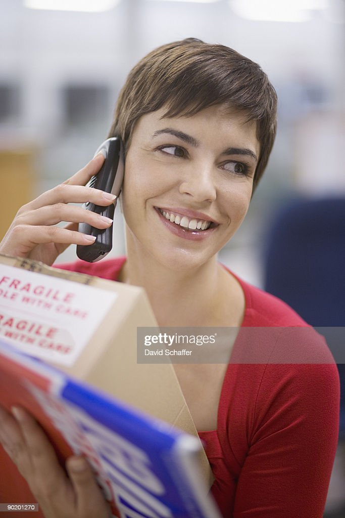 Businesswoman talking on phone and holding box : Stock Photo