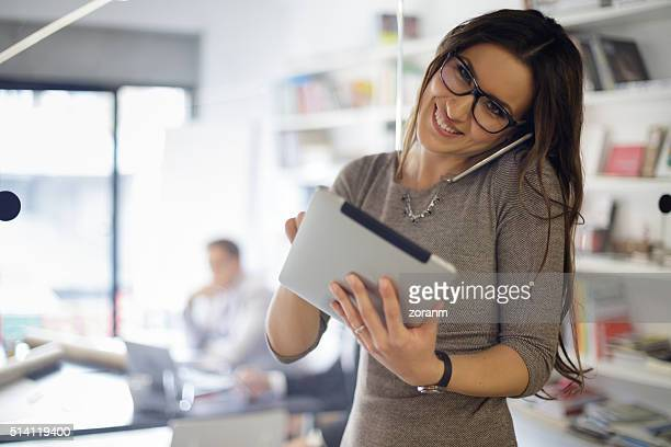 Businesswoman talking on phone and uses digital tablet