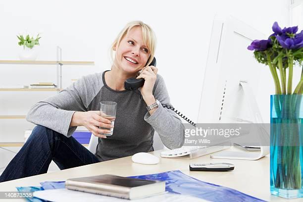 Businesswoman talking on phone at work