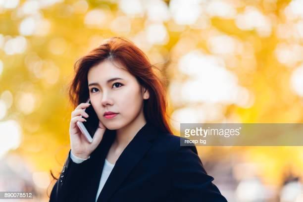 秋の通りに電話で話している実業家