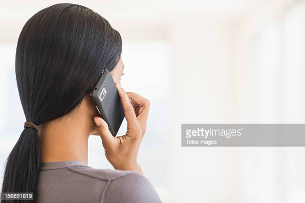 Businesswoman talking on phone, studio shot
