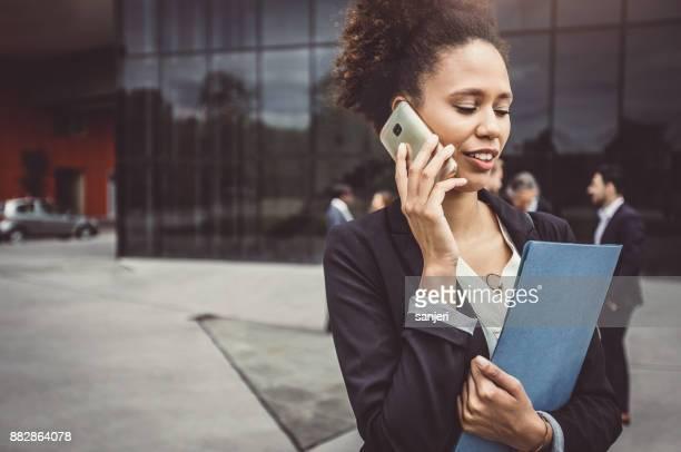 実業家の背後にある同僚と電話で話しています。