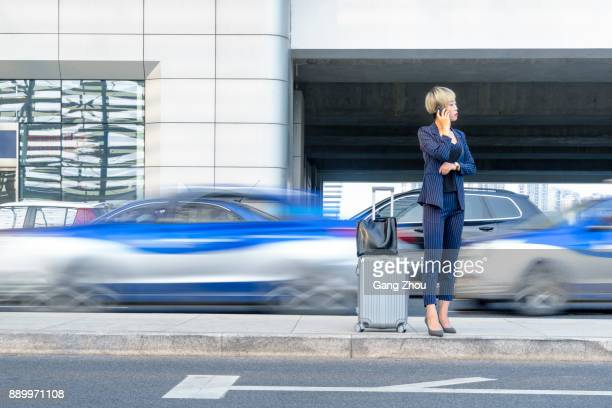 businesswoman talking on phone with suitcase at a bus station