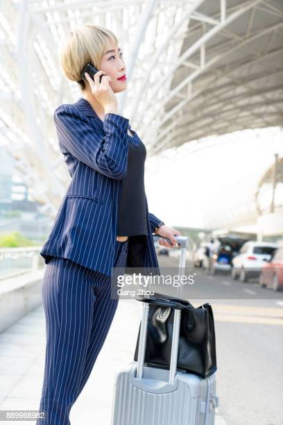 businesswoman talking on phone with suitcase outside airport/station