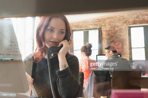 Businesswoman talking on telephone in office