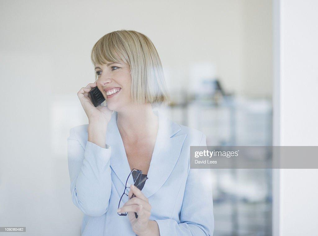 Businesswoman talking on telephone, smiling : Stock Photo