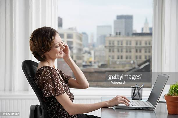 Businesswoman talking on the phone and using laptop