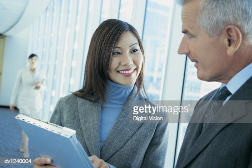 Businesswoman Talking To a Businessman in an Office Corridor : Stock Photo