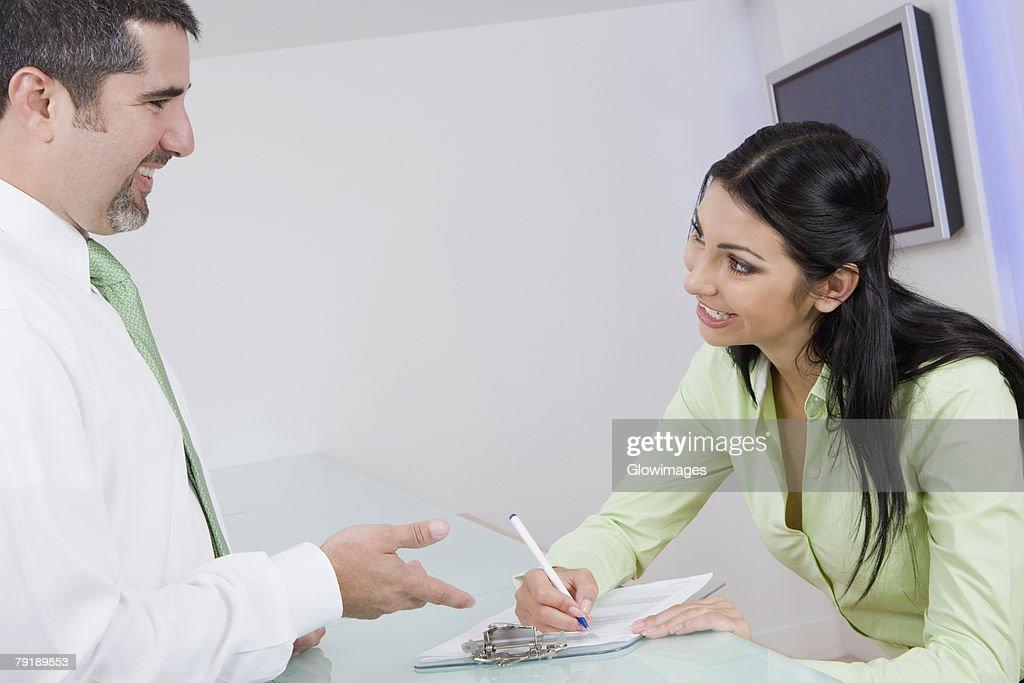 Businesswoman talking to a businessman while writing : Foto de stock