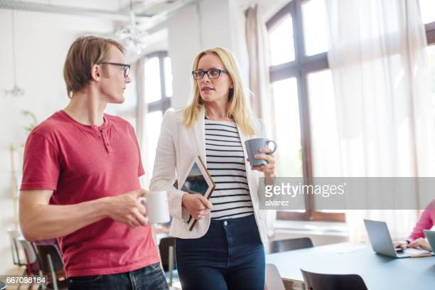 Businesswoman talking to colleague in office