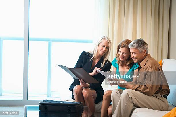 Businesswoman talking to couple on sofa
