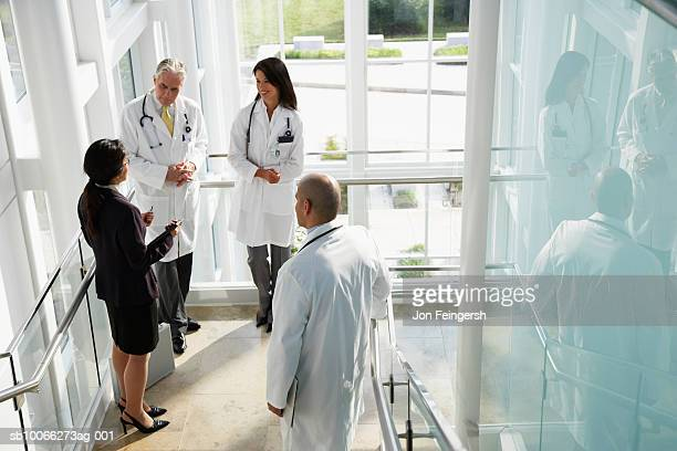 Businesswoman talking to doctors, elevated view