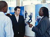 Businesswoman talking with men at exhibition
