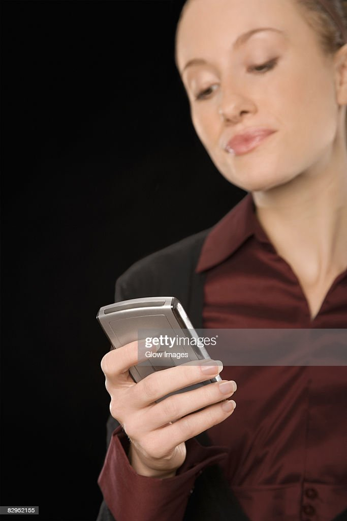 Businesswoman text messaging and smiling : Stock Photo