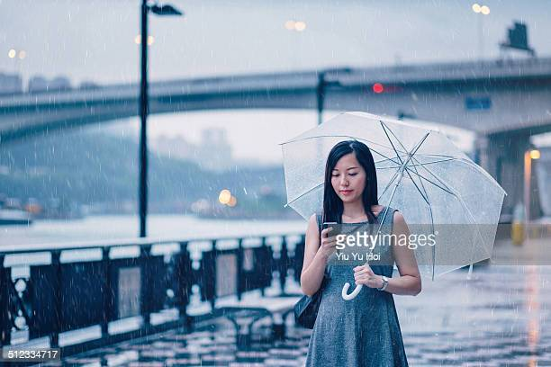 Businesswoman text messaging in rainy city street