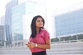 Businesswoman text messaging on mobile phone on city