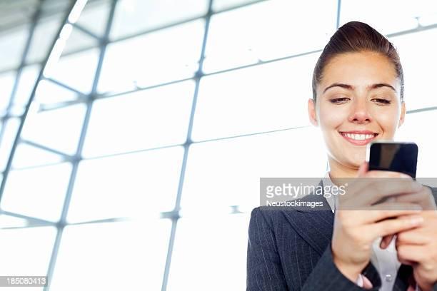 Geschäftsfrau SMS auf einem Flughafen