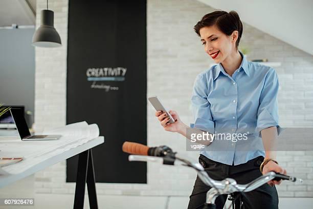 Femme d'affaires SMS dans son bureau.