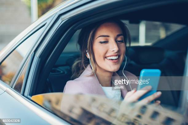 Businesswoman texting in the car