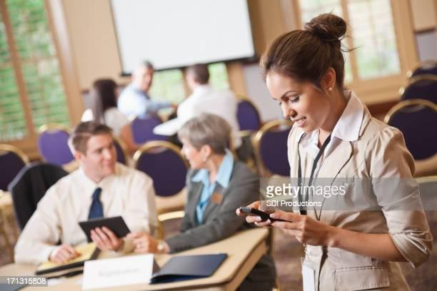 Geschäftsfrau SMS auf Ihr Handy beim Check-in in Konferenz