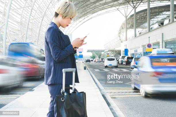 businesswoman texting on phone with suitcase outside airport/station