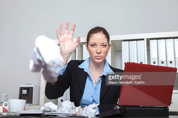 Businesswoman Throwing Crumpled Paper While Sitting At Office