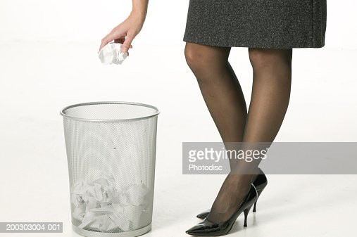 Businesswoman throwing crumpled piece of paper in bin, close-up of bin, close-up, low section : Stock Photo