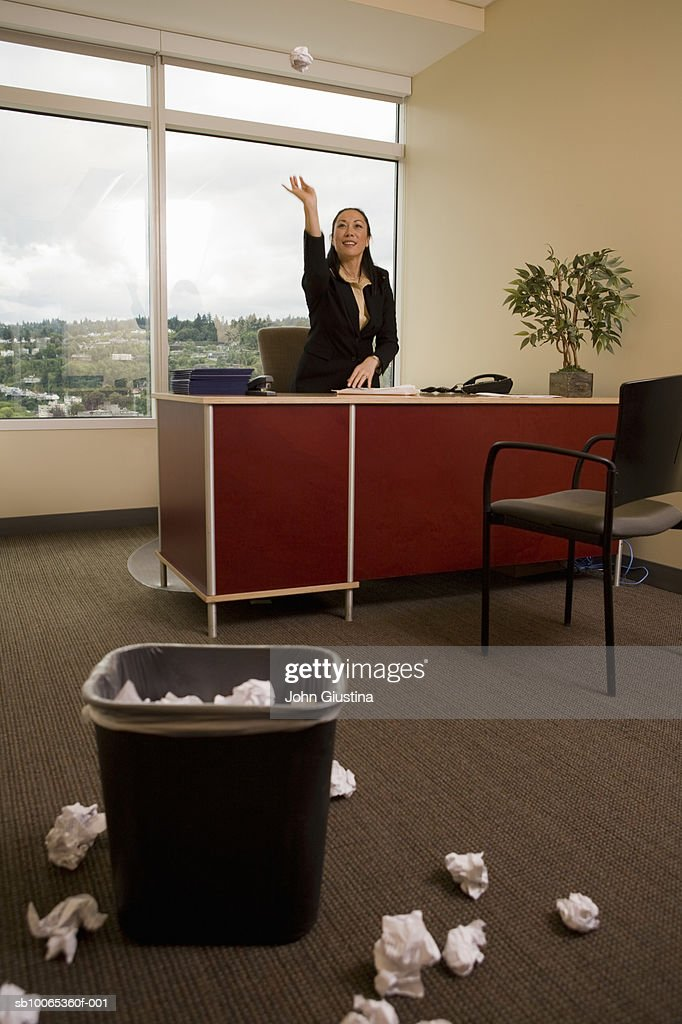Businesswoman throwing crumpled sheet of paper in dustbin
