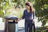Businesswoman throwing garbage in bin at park