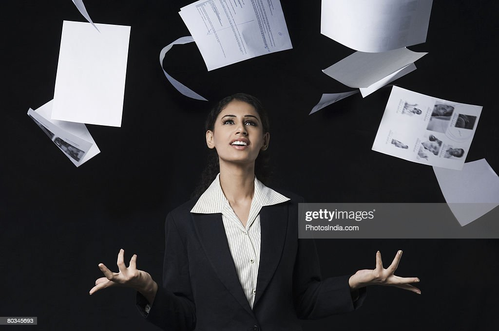 Businesswoman throwing papers in air and smiling : Stock Photo