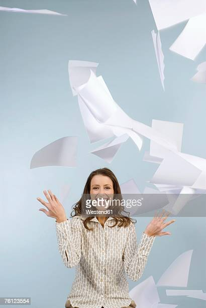 Businesswoman throwing papers in air, smiling, portrait