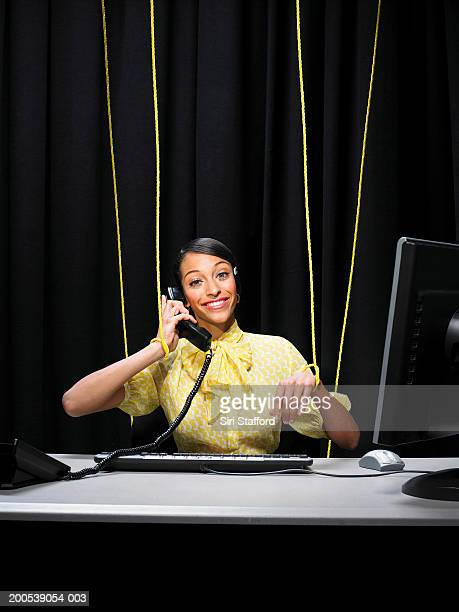 Businesswoman tied up in strings, answering telephone