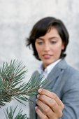 Businesswoman touching plant outdoors