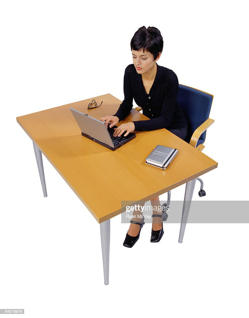 Businesswoman Typing on a Laptop at Her Desk : Stock Photo