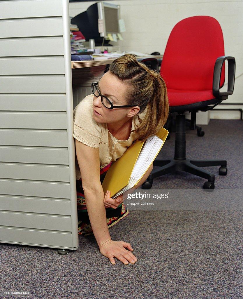 Businesswoman under desk in office, holding yellow folder